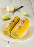 Corncob, butter, lime on white wooden table.  Royalty Free Stock Photo