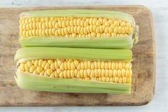 Corncob. Fresh raw corncob on a chopping board Royalty Free Stock Photos