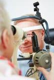 Cornea di misurazione dell'oculista degli anziani immagini stock