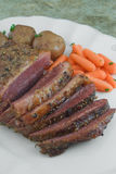 Corned beef brisket. Sliced corned beef brisket on platter with carrots and potatoes Royalty Free Stock Photo