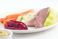 Corned beef and cabbage. Corned beef,cabbage,whole carrots, potatoes and beets artfully arranged on a white plate with mustard on the side Stock Photos