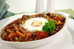 Corned Beef Hash. Baked corned beef hash with egg, tomato and onion with parsley stock images