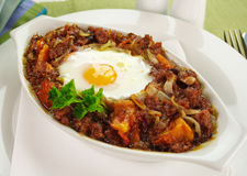 Corned Beef Hash. Baked corned beef hash with egg, tomato and onion with parsley stock image