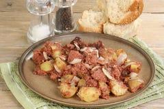 Corned beef and potato hash. Plate of freshly cooked corned beef hash with crusty bread stock photo