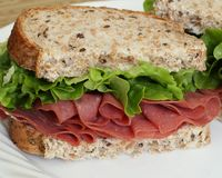 Corned beef sandwich. A delicious corned beef sandwich with fresh leaf lettuce on multi-grain bread stock photos