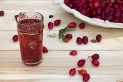 Cornejo rojo en un plato y jugo con hielo Imagen de archivo