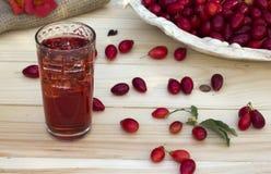 Cornel rojo en un plato y jugo con hielo Imagen de archivo