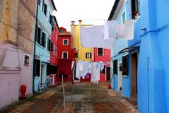 Corner beautifully designed with colorful houses and white clothes to dry in Burano in Venice in Italy. Photo made in the island of Burano in Venice in Italy. In Royalty Free Stock Photography