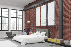 Corner of bedroom interior with brick walls and three narrow vertical posters on them. There is a large bed, an armchair, two lamps and colorful bedside tables Stock Image