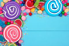 Corner border of colorful assorted candies against blue wood Royalty Free Stock Photo