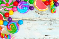 Corner border of colorful candies against rustic wood Stock Images