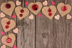 Corner border of Valentines Day burlap hearts over rustic wood. Corner border of Valentines Day burlap hearts with buttons and confetti over a rustic wooden stock photography