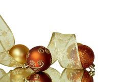 Corner Christmas Ornaments. Corner background decoration of orange and gold Christmall ornaments and ribbon isolated on white royalty free stock photos