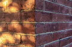 Corner of dark red brick wall with shadows and a lot of space for text Stock Photo
