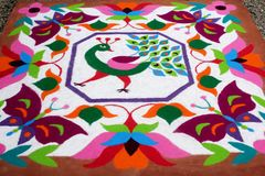 Colourful Rangoli Traditional Floral Design made with Dry Powdered Colours with Peacock, Flowers and Butterflies Stock Images