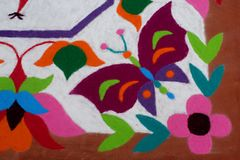 Colourful Rangoli Traditional Floral Design made with Dry Powdered Colours with Peacock, Flowers and Butterflies Stock Photography