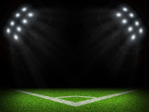 Corner of empty green field with bright spotlights Stock Photos