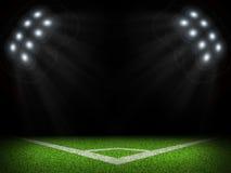 Corner of empty green field with bright spotlights Stock Photos