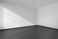Corner of empty room with black parquet floor and white walls Royalty Free Stock Image