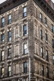 Facade on vintage New York City apartment building. Corner facade on vintage New York City apartment building with brick and windows Royalty Free Stock Photo