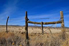 Corner fence post in ranch land. Corner post with a barbed wire fence on ranch land in a desert ranch surrounded by a mountain range stock photo