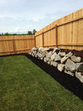 Corner Fence. Corner of small fenced backyard with rock wall. Grass area Royalty Free Stock Images