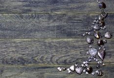 Corner frame border of Hearts beads on dark old wooden background. Royalty Free Stock Images