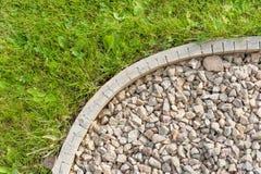 Corner of gravel garden path - construction detail. Detail of garden path showing edging strip, decorative gravel Stock Image