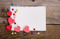 Corner from hearts and colorfull buttons. Corner for empty card from hearts  and  colorfull buttons on wooden background Royalty Free Stock Photo