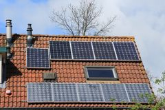 Solar panels on the roof of the house in spring. A corner house with different solar panels on the roof in the residential area in the village Hellevoetsluis in Royalty Free Stock Photos