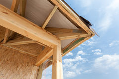 Corner of house with eaves, wooden beams and roof asphalt shingles. Stock Image