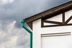 Corner of house with green metal drainpipe Royalty Free Stock Photo