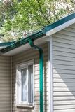 Corner of house with gutter and green metal roof royalty free stock image