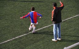 Corner kick. Kid takes a corner in a soccer match while his coach is coaching royalty free stock photos