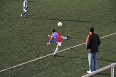 Corner kick. Kids playing soccer on artificial grass. Kid takes a corner kick watched by his coach stock photos