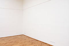 Corner of a large white wall with wooden floor. Tiles Stock Photos