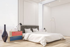 Corner of a master bedroom with a bed, a set of drawers, a tall vase and a large vertical poster. Stock Photo