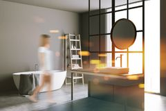Round mirror bathroom, gray walls, angle view blur. Corner of a modern bathroom with loft window, a concrete floor, a sink with a round mirror and a white stock photography