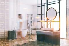 Round mirror bathroom with white walls blur. Corner of a modern bathroom with loft window, a concrete floor, a sink with a round mirror and a white bathtub stock photo