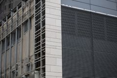 Corner of modern concrete urban building under maintenance with striped grid on wall. Corner of modern concrete urban building under maintenance with striped stock photography