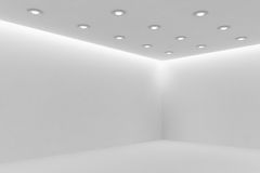 Corner of mpty white room with small round ceiling lamps Royalty Free Stock Photo