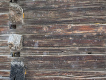 Corner old cabin wall with falling snow background Royalty Free Stock Images