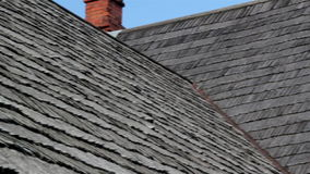 The corner of old cedar wooden shingle shake roof of the house and a clean chimney water tin stock video