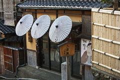 Corner of old Kyoto. Kyoto, Japan - April 8, 2013: Corner of old Kyoto with traditional Japanese paper umbrellas and posters based on Sharaku prints Royalty Free Stock Photos