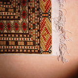 Corner of an oriental rug. A corner and fringe of a patterned oriental rug Stock Photos