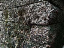 Corner of Rock Wall. Corner: a place or angle where two or more sides or edges meet. rock : the solid mineral material forming part of the surface of the earth stock photo