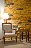 Corner for rest. Part of interior - corner for rest; armchair, side table, lamp and stone wall Stock Images