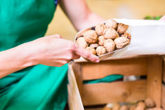 Corner shop clerk filling nuts bags Royalty Free Stock Photos