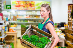 Corner shop clerk filling up storage racks Stock Photo