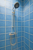 Corner shower cabin. Detail of a corner shower cabin with wall mount shower attachment in blue stock photography